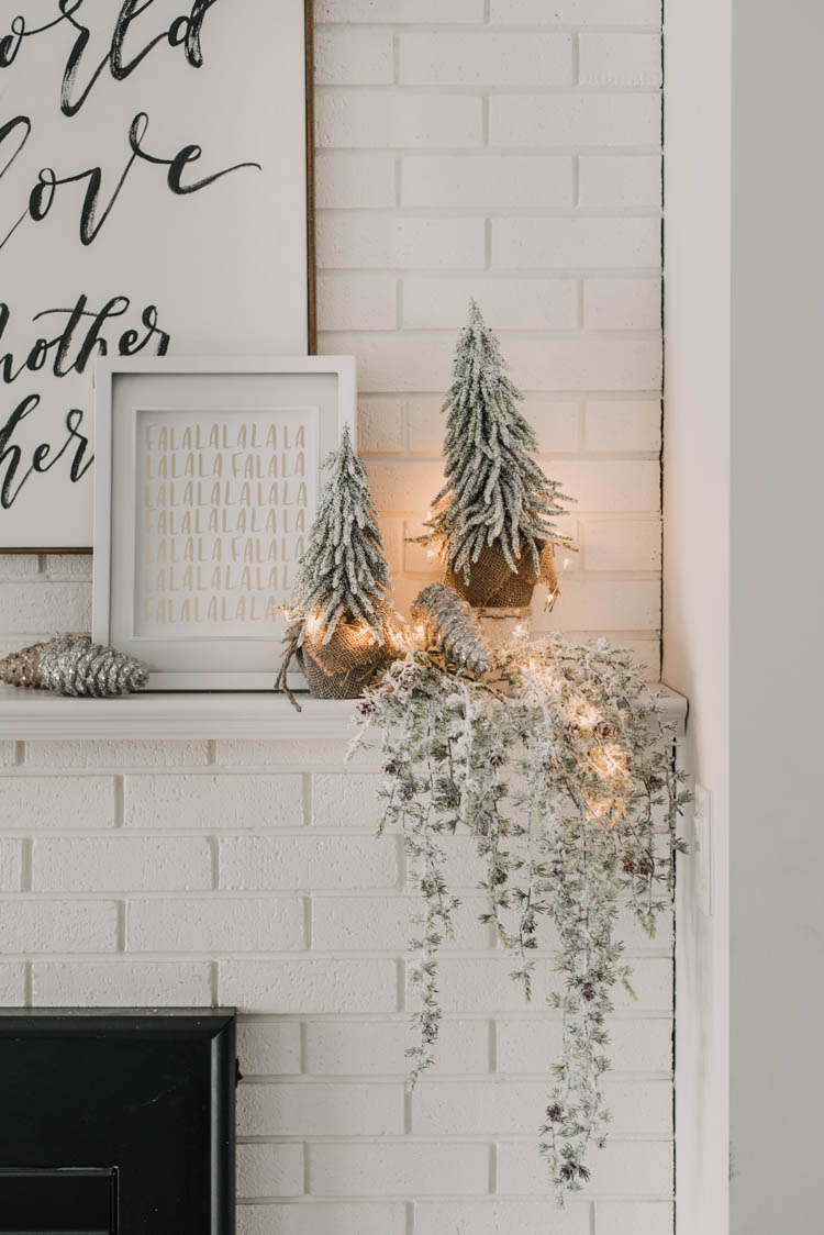 Modern holiday mantel decor... full of black, white, metallics, and frosted greenery