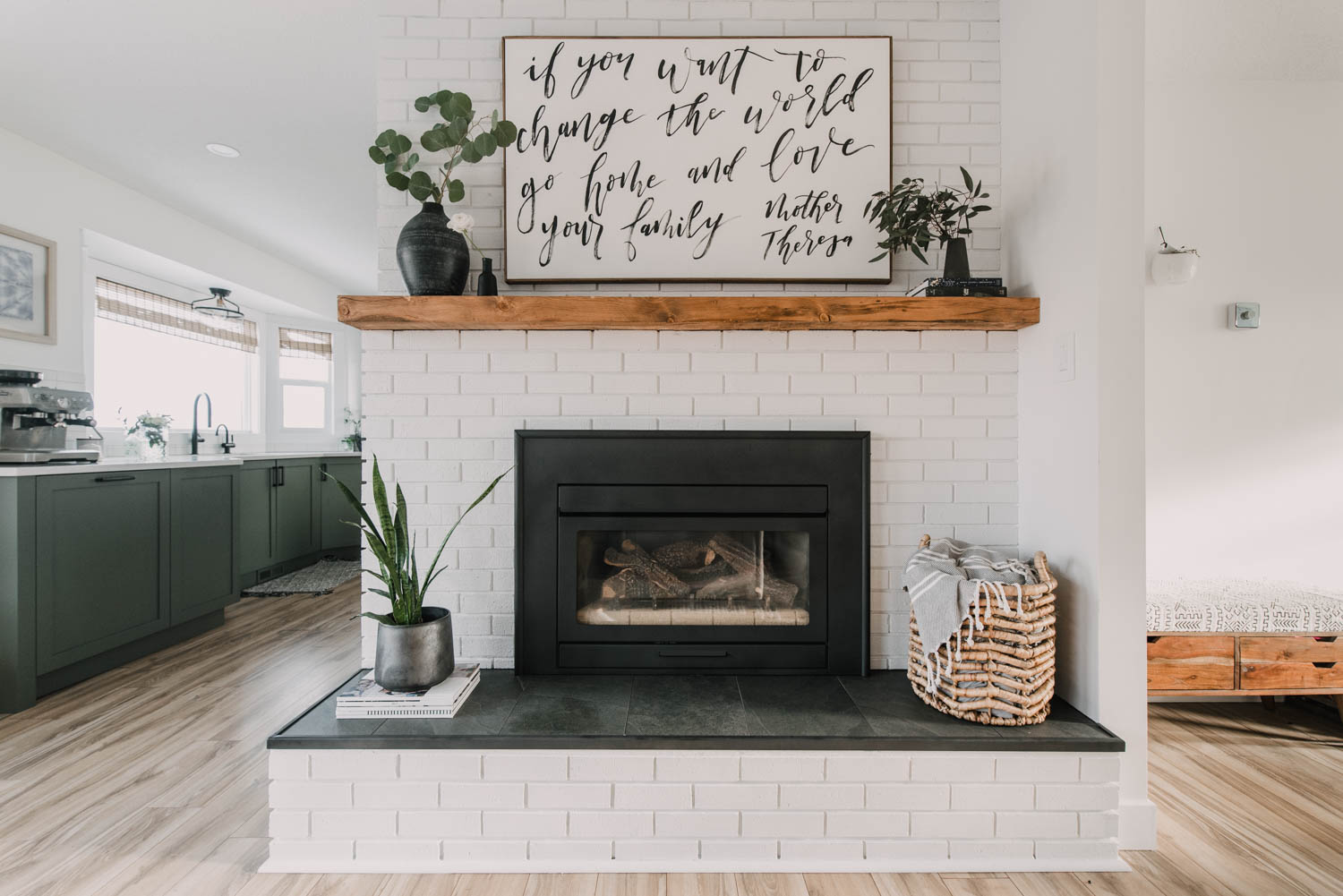 Painted brick fireplace with rustic wood mantel and tile hearth