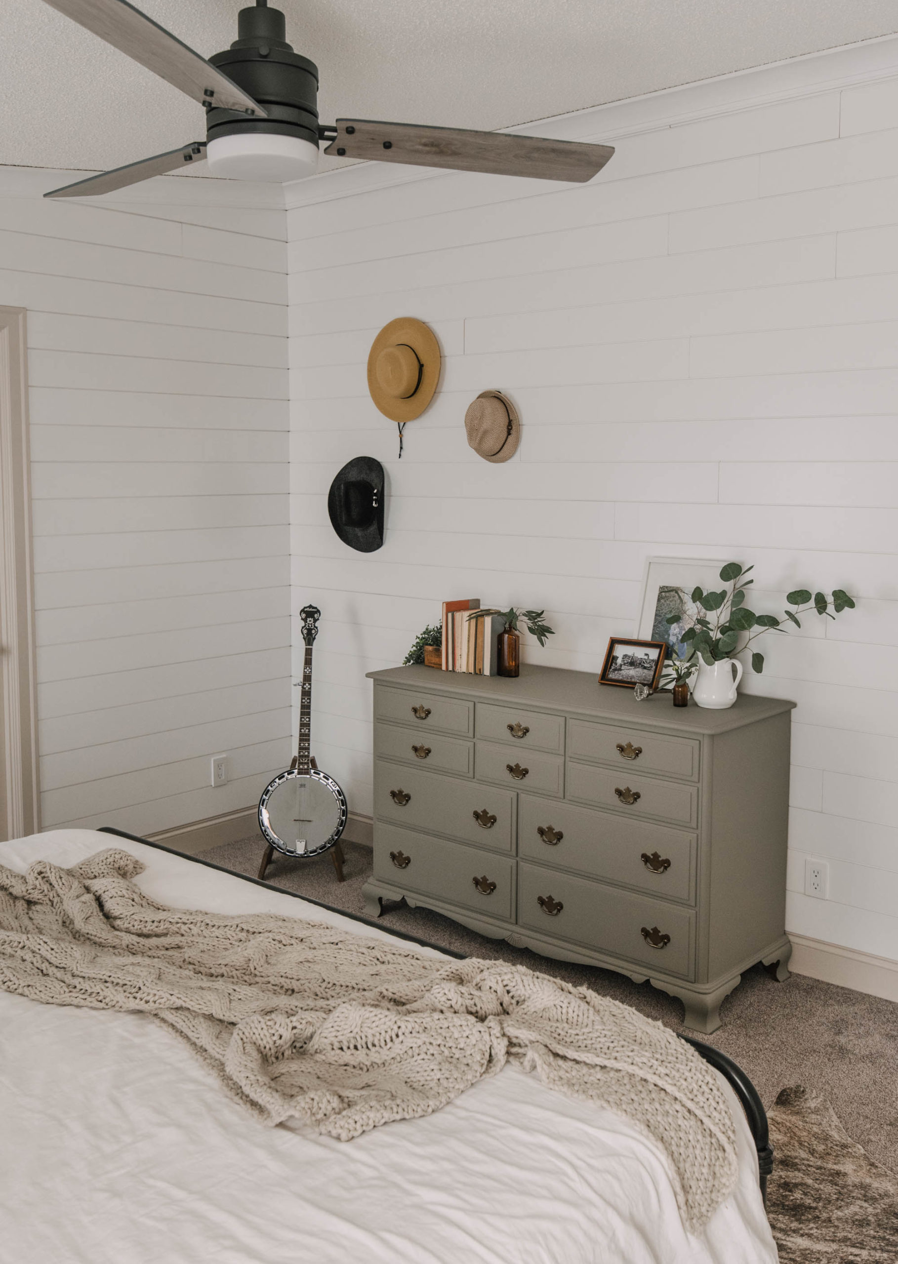 Green Painted dresser with hat wall in a shiplap bedroom