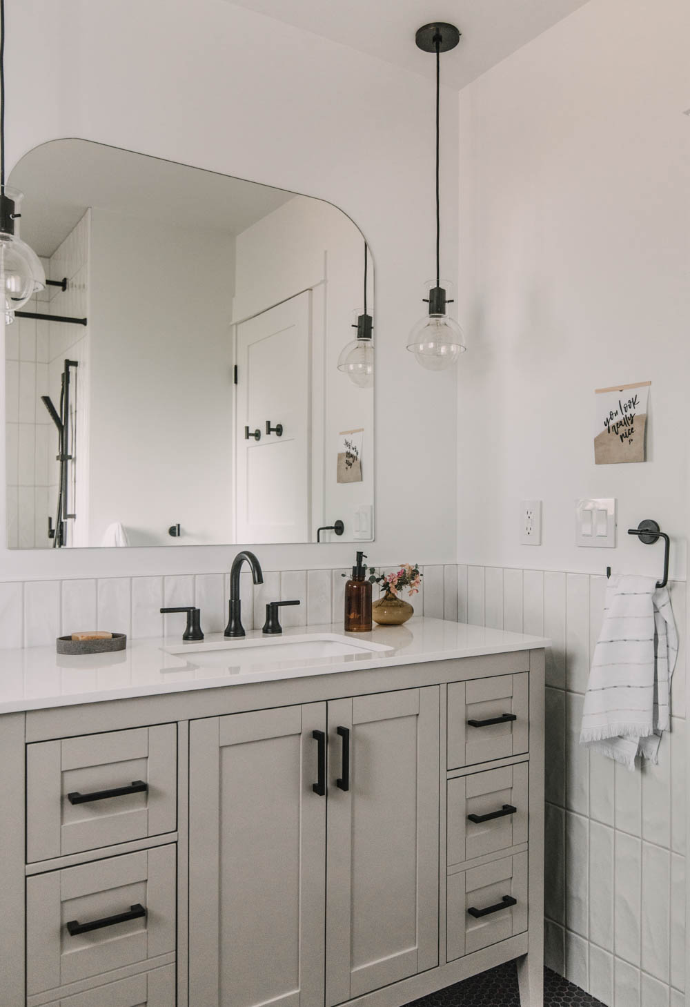 pendant lights with an arch mirror over the vanity