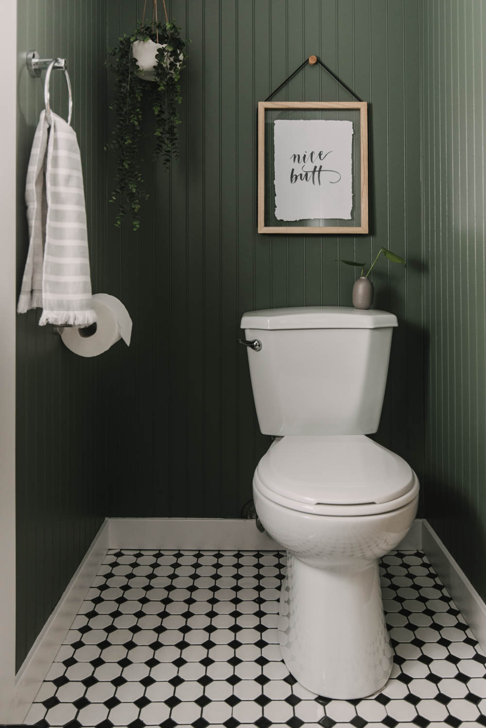 green bathroom with beadboard and black and white tiles.