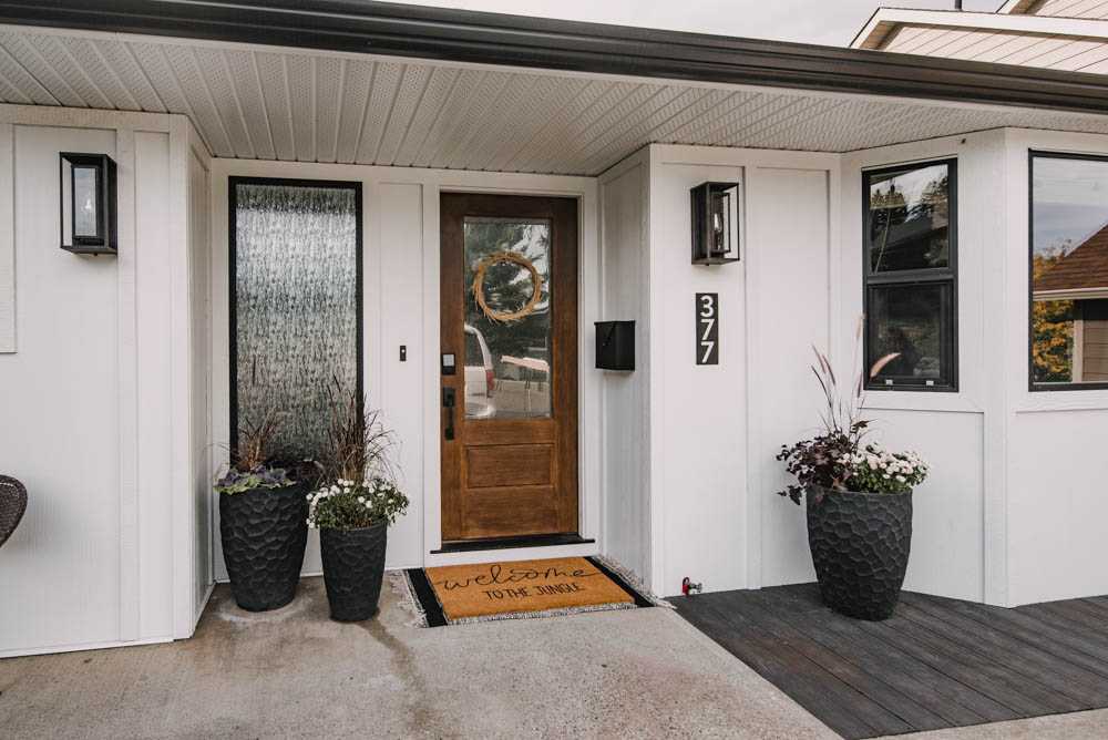 Modern ranch house entryway with black and white and warm wood tones