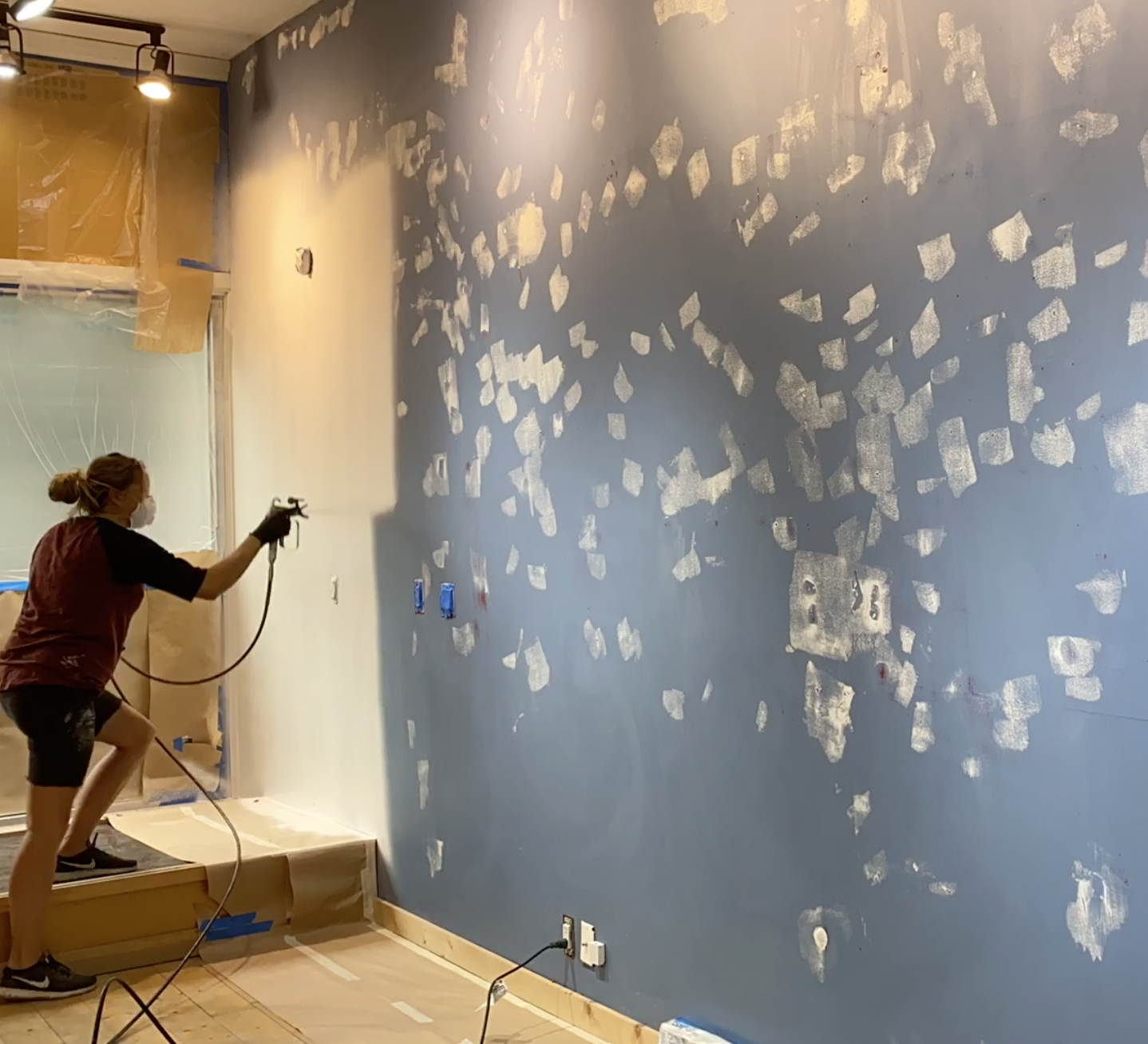 Wagner Control Pro 130 in action painting a blue wall with patches white