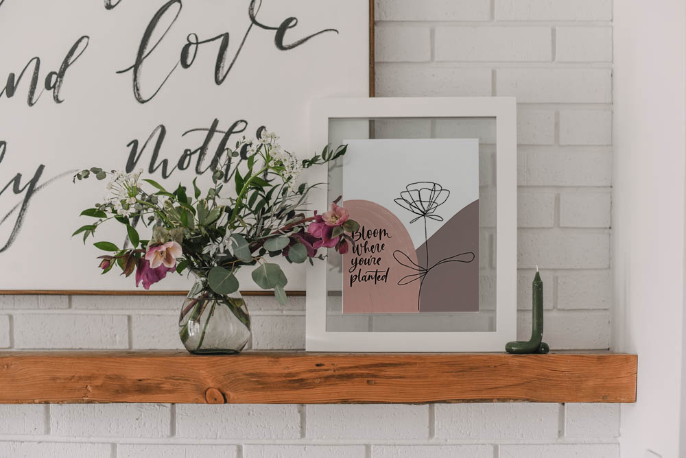 hand lettered modern art reads 'bloom where you are planted' in frame on mantel