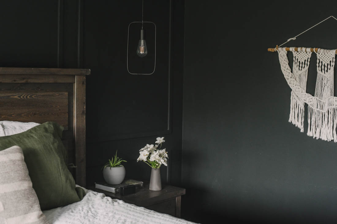 Black moulding wall with pendant lights over nightstand