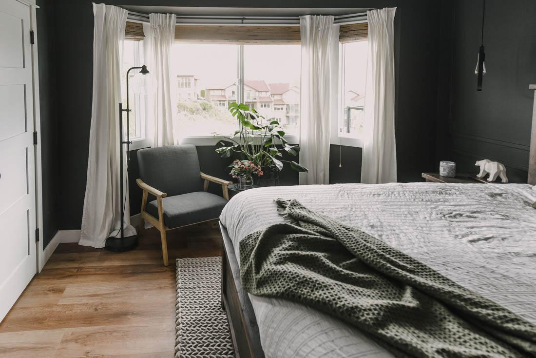 Black bedroom decor with a cozy bay window