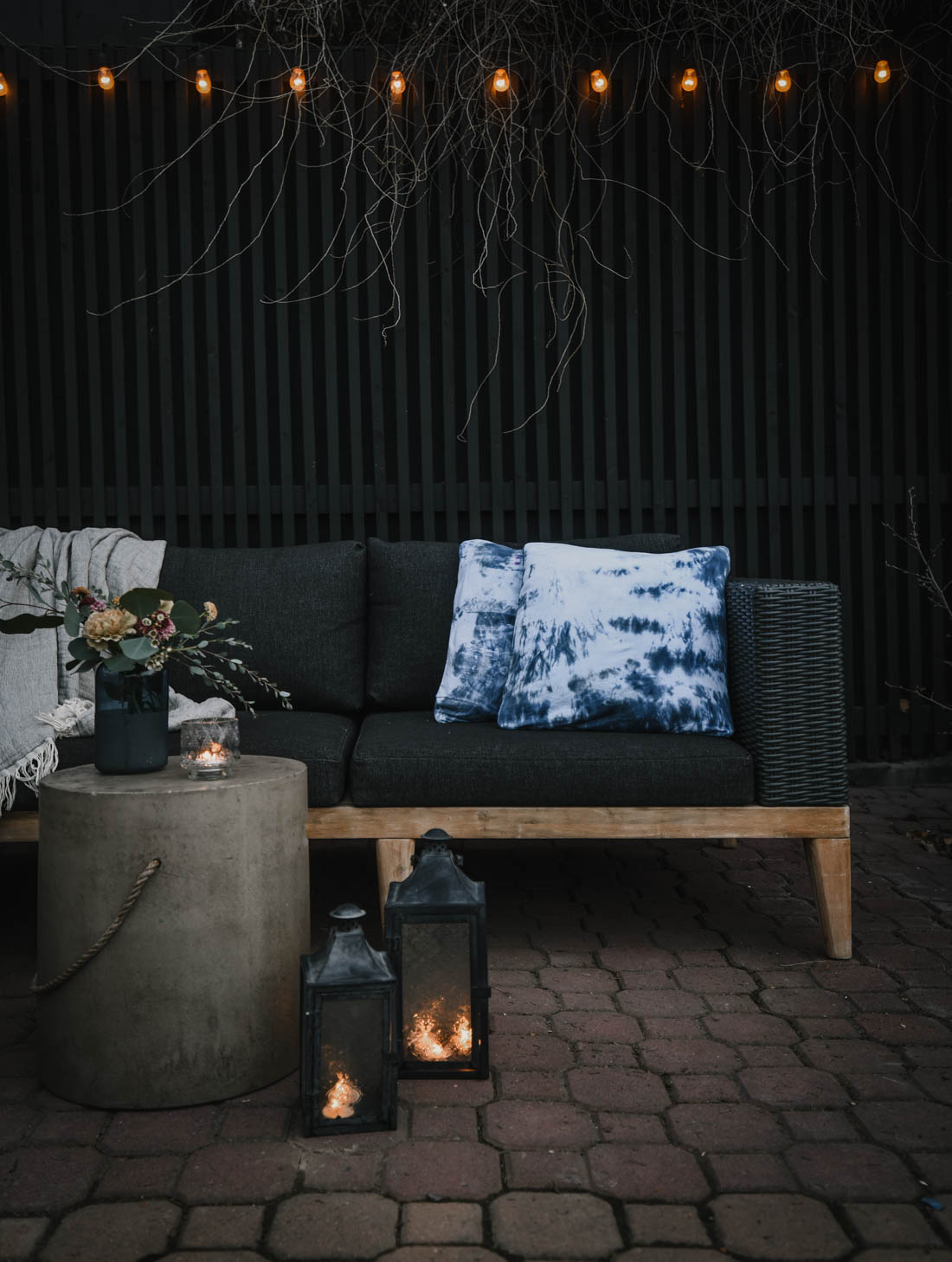 Moody brick patio with tie dye and a charcoal sectional