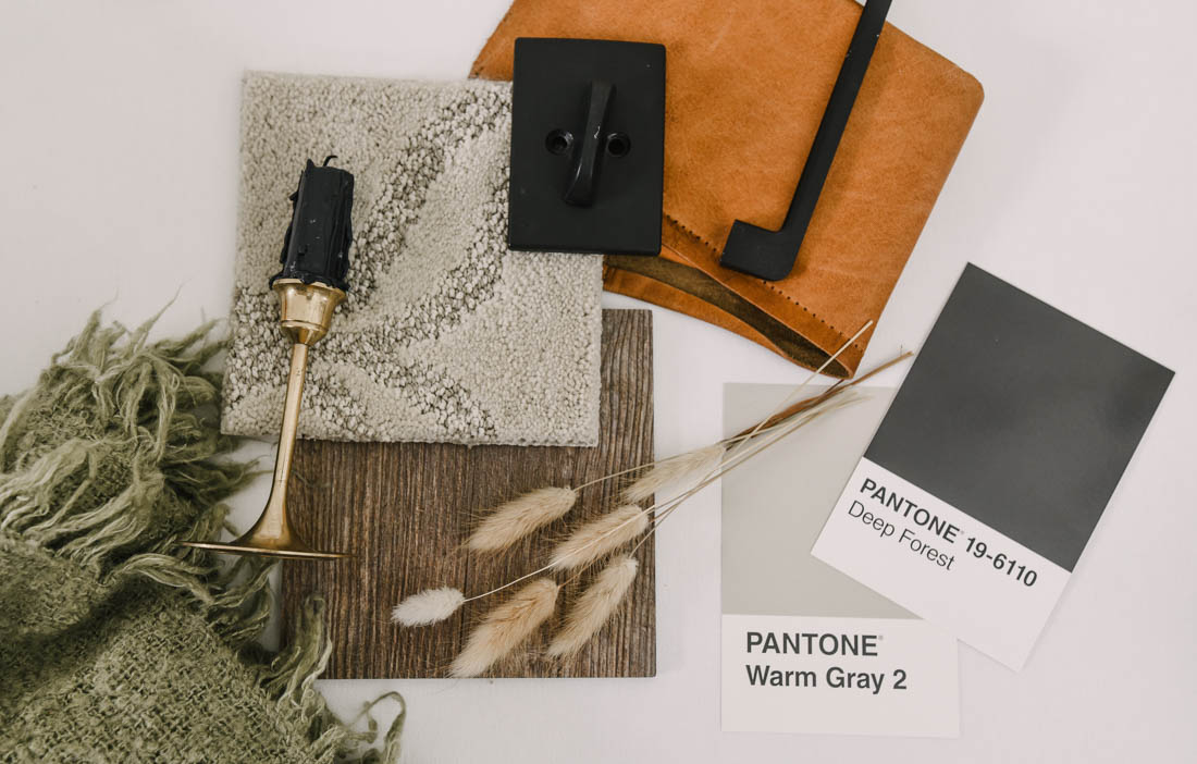rustic leather, black hardware, and tan carpet with medium wood in a flatlay
