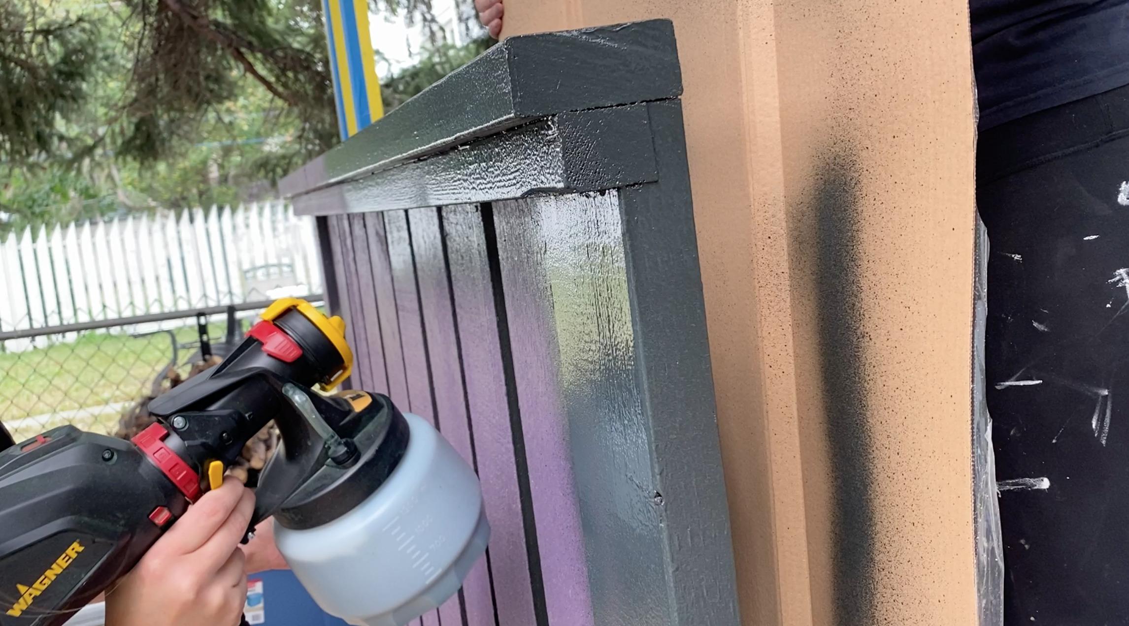 spraying bottom edge of railing with a sprayer