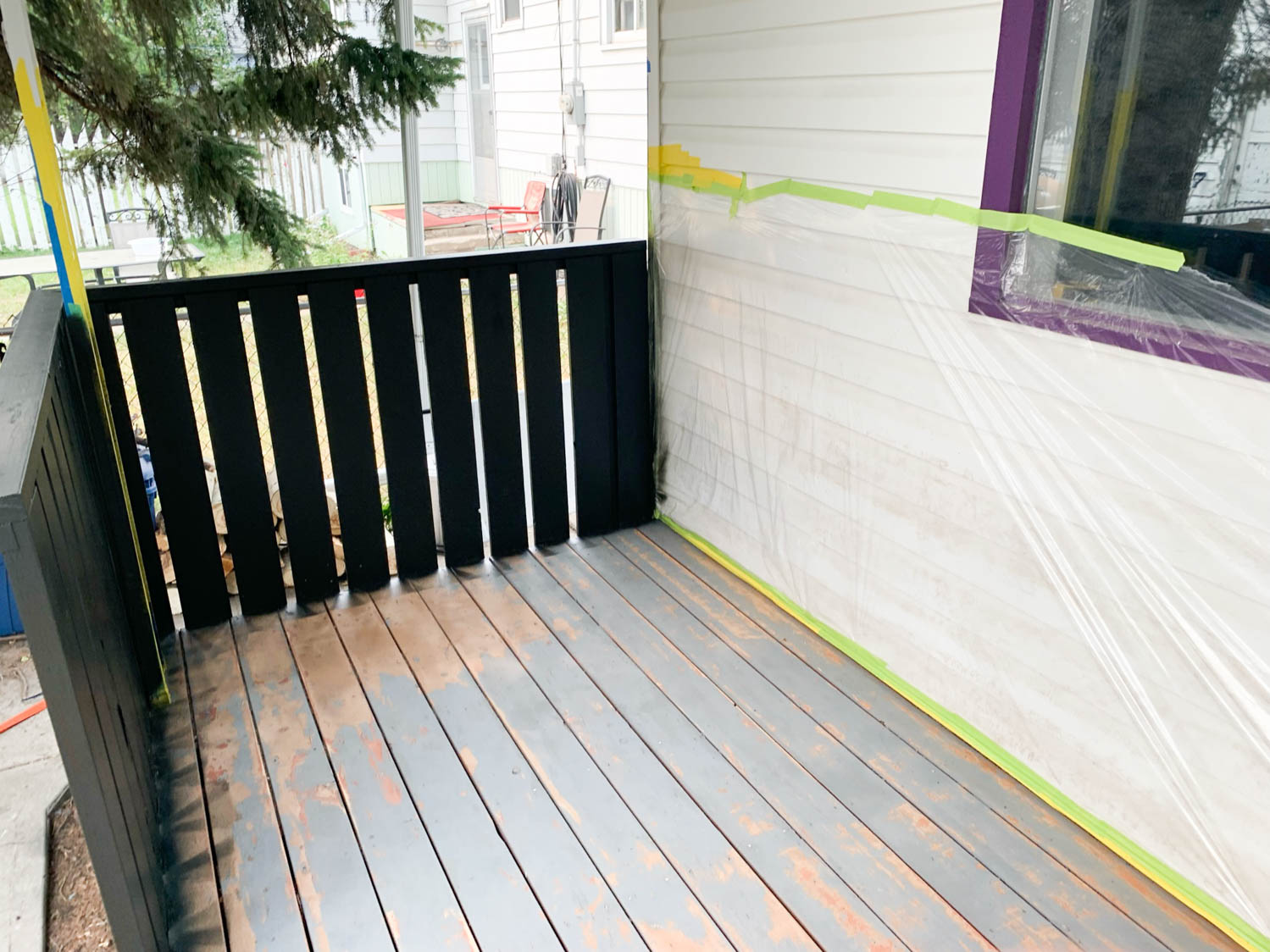 Painting a deck railing with a paint sprayer