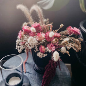dried floral arrangement with pink strawflowers and bunny tail grasses